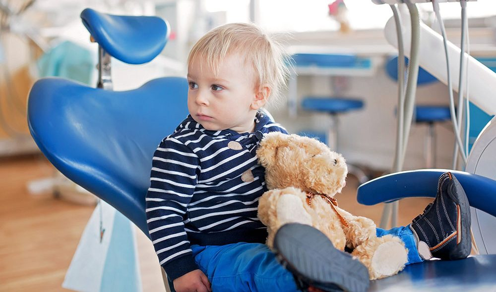 Little toddler boy with teddy bear toy at dentist's clinic for routine check-up, child alone sitting on dentist chair